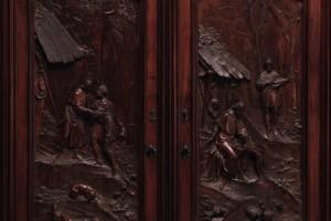 Sulle due porte dell'armadio sono narrati due degli episodi più noti della vita di san Rocco: il momento in cui Gottardo Pollastrelli scopre il proprio cane che porta il cibo al santo, che, malato,si era ritirato in un bosco nei dintorni di Piacenza e il successivo incontro tra i due. Gli intagli si pongono tra le realizzazioni più notevoli dello stile narrativo di Marchiori.